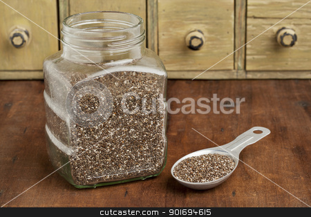 jar and tablespoon of chia seeds stock photo, chia seeds in glass jar and on measuring aluminum tablespoon with a vintage drawer cabinet in background by Marek Uliasz