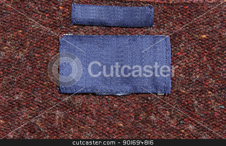 Red and Maroon Shirt Label stock photo, A red sweater with blue labels.  by Chris Hill