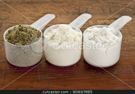 scoops of protein powder stock photo, plastic measuring scoops of three protein powders (from left hemp seed, whey concentrate, whey isolate) on a grunge wood surface by Marek Uliasz