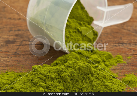 wheatgrass powder supplement stock photo, wheatgrass powder spilling of a plastic measuring scoop against grunge wood background by Marek Uliasz