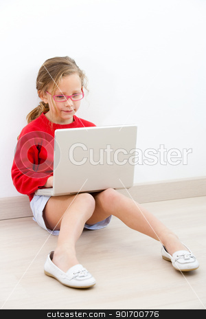Young girl at home with laptop. stock photo, Portrait of cute blond girl doing homework at home with laptop.  by karel noppe