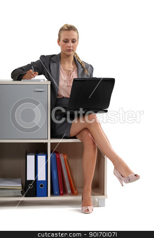 Woman sat with laptop on book case stock photo, Woman sat with laptop on book case by photography33