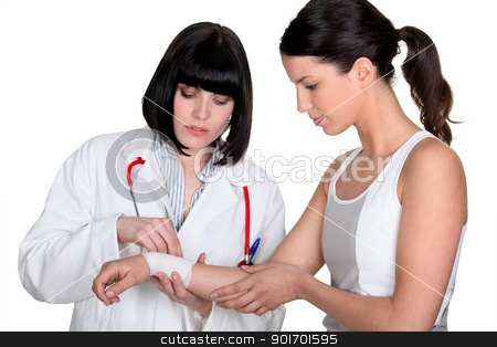 Doctor bandaging patient's wrist stock photo, Doctor bandaging patient's wrist by photography33
