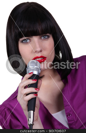 Brunette singing into microphone stock photo, Brunette singing into microphone by photography33