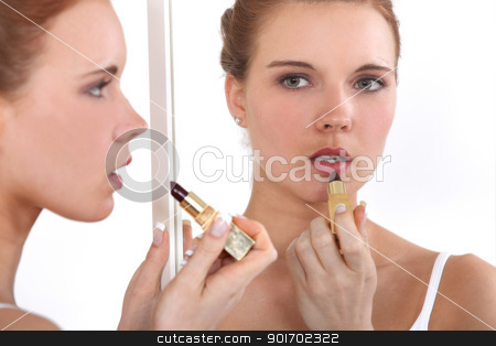 Woman applying lipstick in mirror stock photo, Woman applying lipstick in mirror by photography33