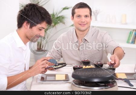 Two men enjoying a Raclette stock photo, Two men enjoying a Raclette by photography33