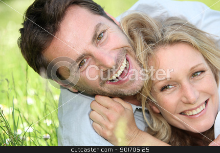 Couple laughing on the grass. stock photo, Couple laughing on the grass. by photography33