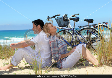 couple on the beach with bikes stock photo, couple on the beach with bikes by photography33