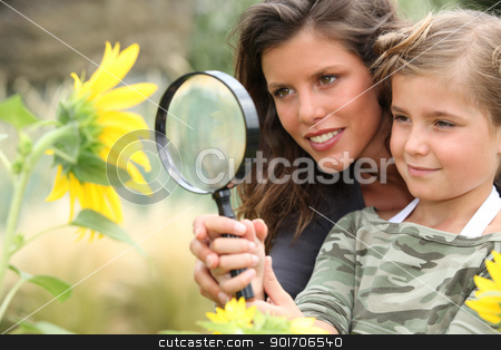 Young mum and daughter looking at a sunflower through a magnifying glass stock photo, Young mum and daughter looking at a sunflower through a magnifying glass by photography33