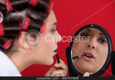 Woman wearing hair rollers applying make-up stock photo, Woman wearing hair rollers applying make-up by photography33
