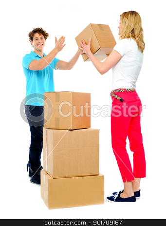 Team work. Couple helping each other stock photo, Woman passing cardboard cartons to man  while he stacks them by Ishay Botbol