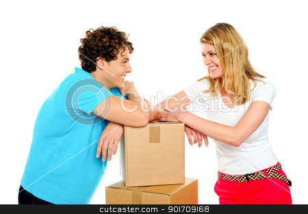 Lets make love, forget work stock photo, Lovable young smiling couple with boxes looking into each others eyes. Love concept by Ishay Botbol   