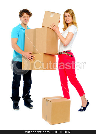 Lovely couple holding cardboard boxes stock photo, Handsome guy holding stack of cardboard boxes while woman doing the placement by Ishay Botbol   