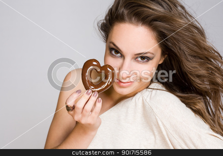 Brunette beauty with heart shaped chocolate. stock photo, Portrait of a brunette beauty with heart shaped chocolate cookie. by exvivo