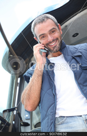 Farmer standing in the cab of his tractor talking on a cellphone stock photo, Farmer standing in the cab of his tractor talking on a cellphone by photography33