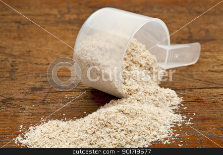scoop of psyllium seed husks  stock photo, psyllium seed husks - dietary supplement, source of soluble fiber, measuring scoop over grunge wood background by Marek Uliasz
