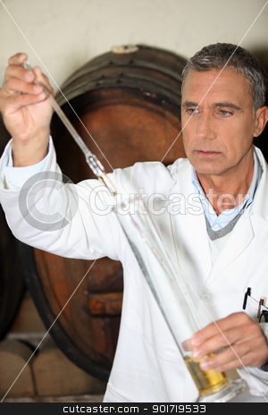 Man testing brandy in a cellar stock photo, Man testing brandy in a cellar by photography33