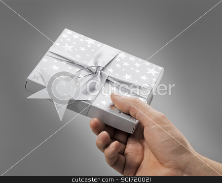 A Gift for You stock photo, Man holding a gift box (contains a CD) in his hand. by Stocksnapper
