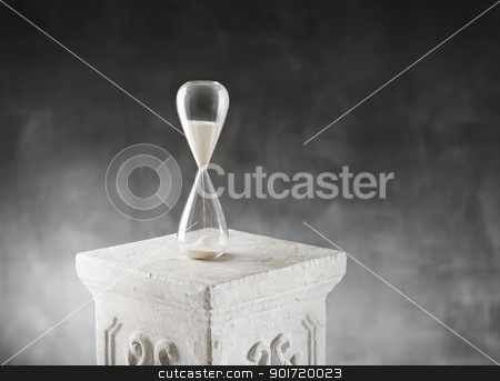 Hourglass stock photo, Hourglass on a plaster column. by Stocksnapper