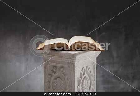 Open Book stock photo, Old book opened on a plaster column. by Stocksnapper
