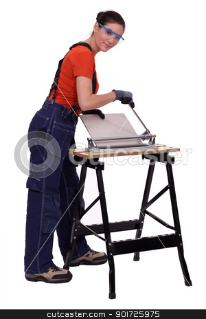 Woman cutting tiles stock photo, Woman cutting tiles by photography33