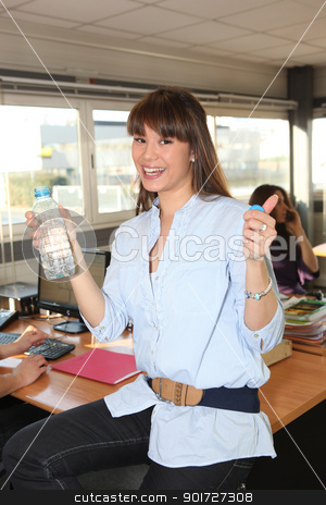 Brunette drinking bottle of water at work stock photo, Brunette drinking bottle of water at work by photography33