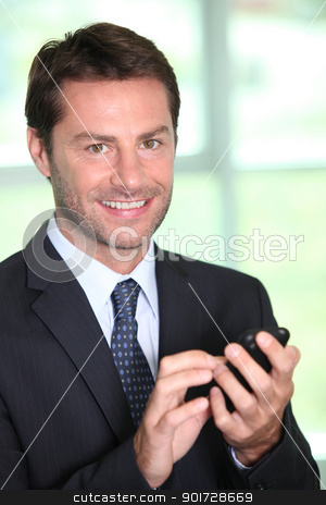 A smiling businessman about to make a phone call. stock photo, A smiling businessman about to make a phone call. by photography33