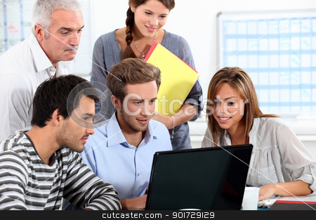 Informal team of people sitting round a laptop computer stock photo, Informal team of people sitting round a laptop computer by photography33