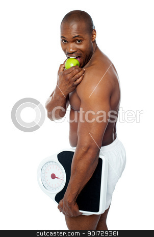 Young man enjoying fresh green apple stock photo, Young man enjoying fresh green apple and holding weighing scale in one hand by Ishay Botbol   