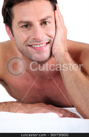 Naked man lying on massage table stock photo, Naked man lying on massage table by photography33