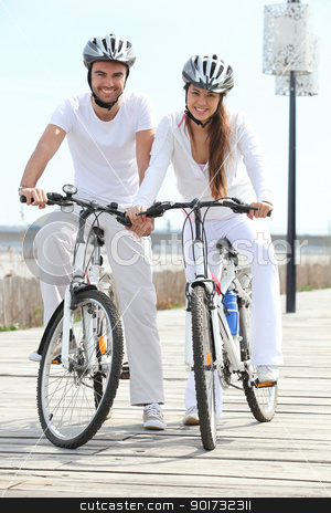 couple riding bicycle wearing cycle helmet stock photo, couple riding bicycle wearing cycle helmet by photography33