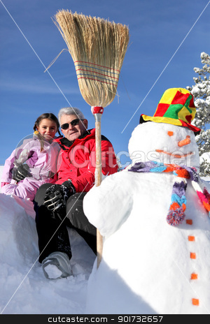 Father and daughter stood with snowman stock photo, Father and daughter stood with snowman by photography33