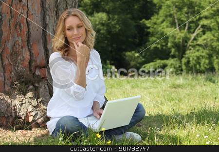 Woman using laptop in park stock photo, Woman using laptop in park by photography33