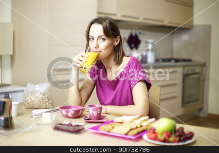 Portrait of female model drinking orange juice at home during breakfast stock photo, Beautiful woman in pajamas having breakfast with fresh fruit cereals buiscuits and orange juice by federico marsicano