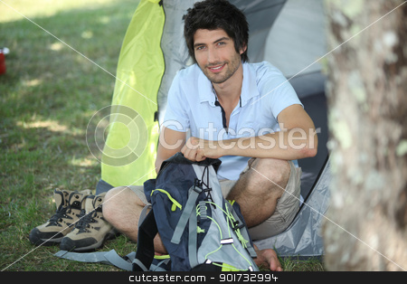 Man sitting in front of his tent stock photo, Man sitting in front of his tent by photography33
