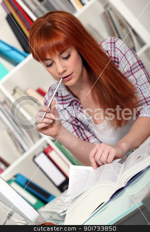 Redhead studying hard for her exams stock photo, Redhead studying hard for her exams by photography33