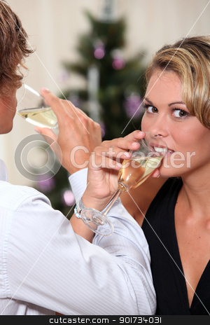 a blonde woman and a man crossing arms and toasting with sparkling wine flutes stock photo, a blonde woman and a man crossing arms and toasting with sparkling wine flutes by photography33