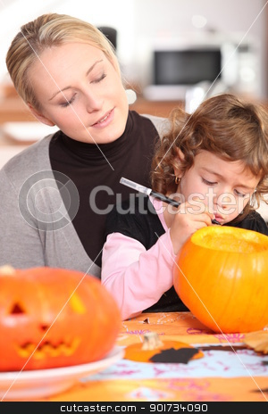 Little girl carving out pumpkin for Halloween stock photo, Little girl carving out pumpkin for Halloween by photography33