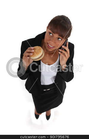 businesswoman eating a hamburger and talking on her cell stock photo, businesswoman eating a hamburger and talking on her cell by photography33