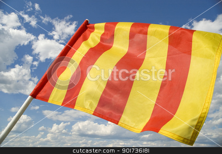 Yellow flag. stock photo, Yellow flag on a background of the dark blue sky with clouds. by Yury Ponomarev