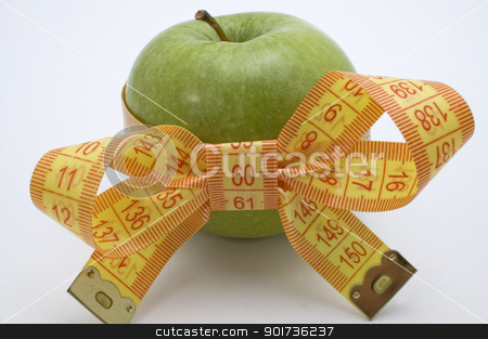 Symbol of diet and healthy eating. stock photo, Green Apple with measuring tape. by Yury Ponomarev