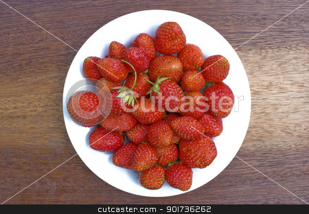 Strawberry. stock photo, Red, ripe wild strawberry in a white plate on a brown background. by Yury Ponomarev