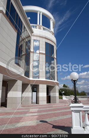 Glass facade and balcony with columns. stock photo, Balcony with columns on a background of the sky with clouds. by Yury Ponomarev