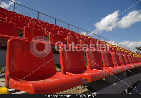 Lines of color seats. stock photo, Red seats on a background of the sky with clouds. by Yury Ponomarev