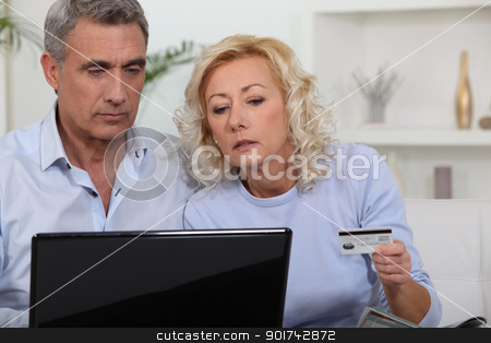 Middle aged couple shopping online. stock photo, Middle aged couple shopping online. by photography33