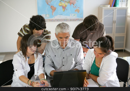 Teacher and a group of pupils sitting round a laptop stock photo, Teacher and a group of pupils sitting round a laptop by photography33