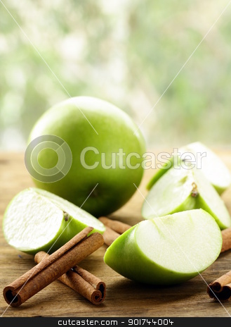 green apples and cinnamon sticks on a wooden background stock photo, green apples and cinnamon sticks on a wooden background by Olga Kriger