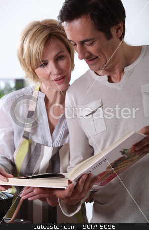 Couple looking at cookery book stock photo, Couple looking at cookery book by photography33
