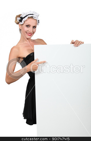 Woman in a French maid's outfit pointing at a blank board ready for text stock photo, Woman in a French maid's outfit pointing at a blank board ready for text by photography33