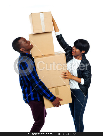 Teenage couple with cardboard boxes stock photo, Teenage couple with cardboard boxes. Girl trying to make stack high by Ishay Botbol